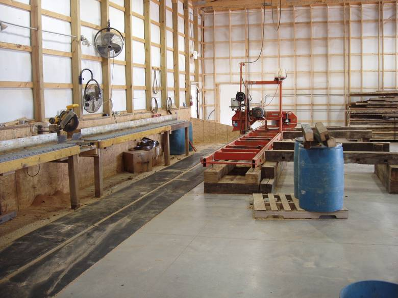 Wood-Mizer and end-cut station / The concrete floor is hard--they have put down rubber runners
